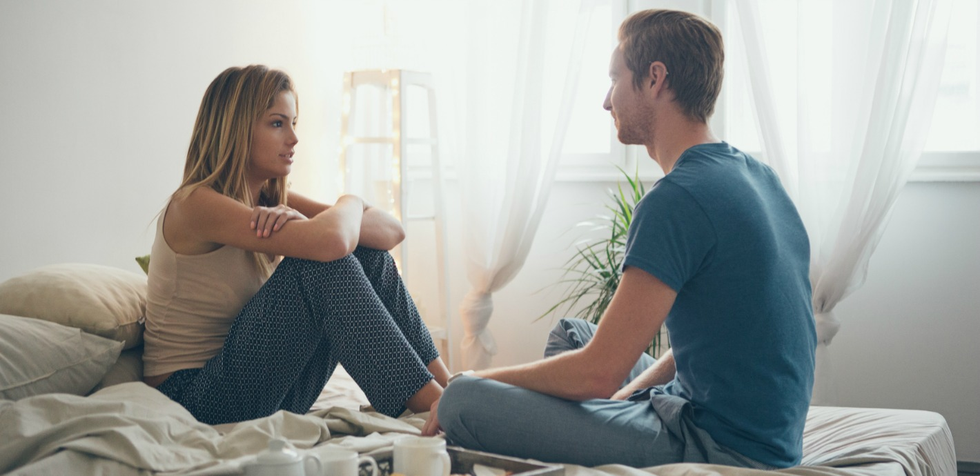 Young couple sitting on the bed and talking. - Strong Connections